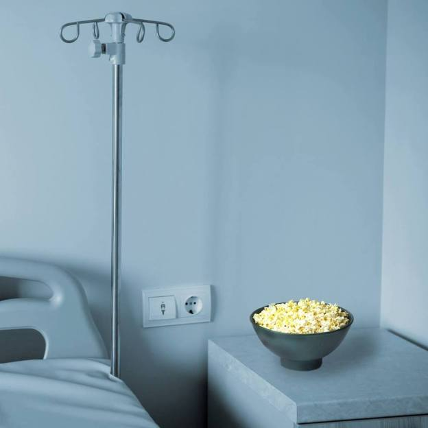 Empty hospital bed with bowl of popcorn on the stand
