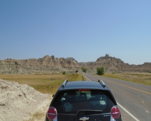 Photo of black car from the back looking toward the road, SD Badlands NP in the distance